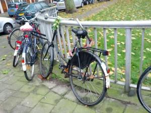 En rusten cykel med tre låse spændt fast til hegn