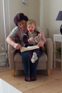 Farmor er i gang med at strikke et tæppe til dukke Sally og viser her fremskridtet