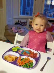 Ida er fanget et kort øjeblik ved spisebordet før hun stikker af for at lege