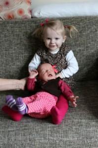 Den stolte storesøster sidder med Lillesøster for første gang
