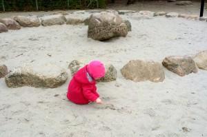 Ida har fundet ud af at man kan tegne i sandet med en pind