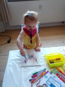 Stuen er omdannet til kunstzone med voksdug så Ida kan lege og tegne alene, mens Mor ammer Maya
