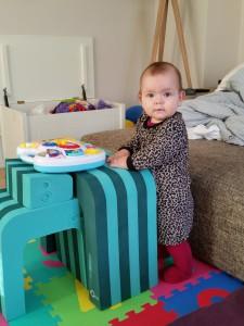 Maya kan selv stå, gå lidt frem og tilbage ved sofaen og dreje sig fra bobles-bordet og over på sofaen