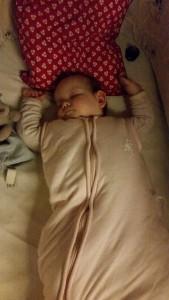 Maya med begge hænder over hovedet i søvne - næsten som en helt almindelig baby