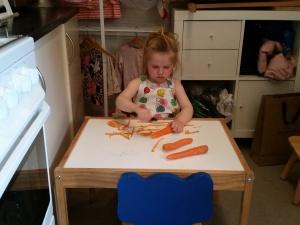Ida meget koncentreret om at skrælle gulerødder