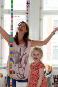 Mor og pigerne har lavet et Lego-tårn så højt at ikke engang Mor kunne nå toppen til sidst