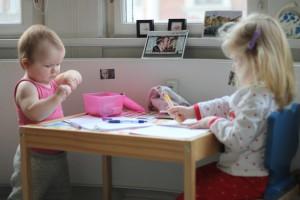 Søstre, der morgenhygger med tuscher i nattøj